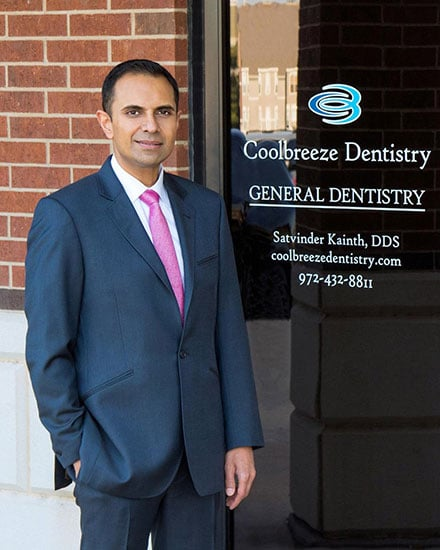 Dr. Kainth in front of his dental office